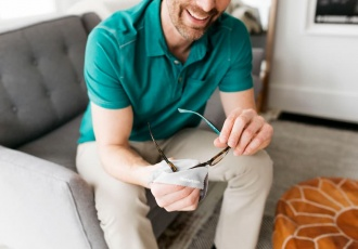 man sitting on couch cleaning glasses with cloth