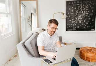 man wearing glasses sitting on couch working on computer