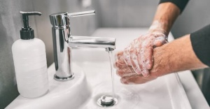 soapy hands under running water in sink