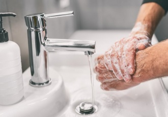 soapy hands in sink with running water
