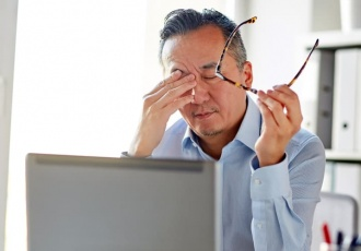 man at desk holding glasses and rubbing eyes